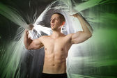 Young strong man in studio with green ab — Stock Photo