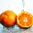 Mandarine in the sparks of water — Stock Photo