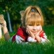 Stock Photo: The small beautiful girl on a green lawn