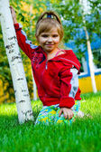 The small beautiful girl on a green lawn — Stock Photo