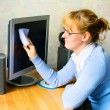 Royalty-Free Stock Photo: The girl wiping the monitor