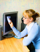 The girl wiping the monitor — Stock Photo