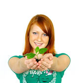 Beautiful young woman holding plant — Stock Photo