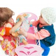 Two little girls divide a doll — Stockfoto