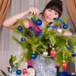The girl decorates fur-tree branches - Stock Photo
