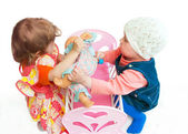 Two little girls divide a doll — Stock Photo
