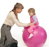 The woman swings the child on fitball — Stock Photo
