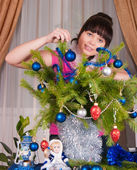 The girl decorates fur-tree branches — Stok fotoğraf