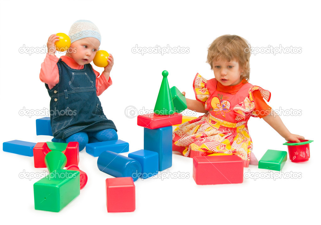 Two girls play cubes on a white background — Stock Photo #1900364
