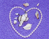 Heart from pearls on lilac background — Stock Photo