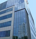 New glass reflective building, blue sky — Stock Photo