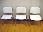 Few white chairs on wood floor — Stock Photo
