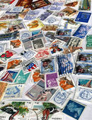 Heap of different colorful post stamps — Stock Photo