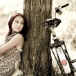 Royalty-Free Stock Photo: Beautiful girl sitting near bike and tree at rest in forest. Photo in retro