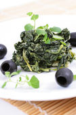 Spinach with black olives — Stock Photo