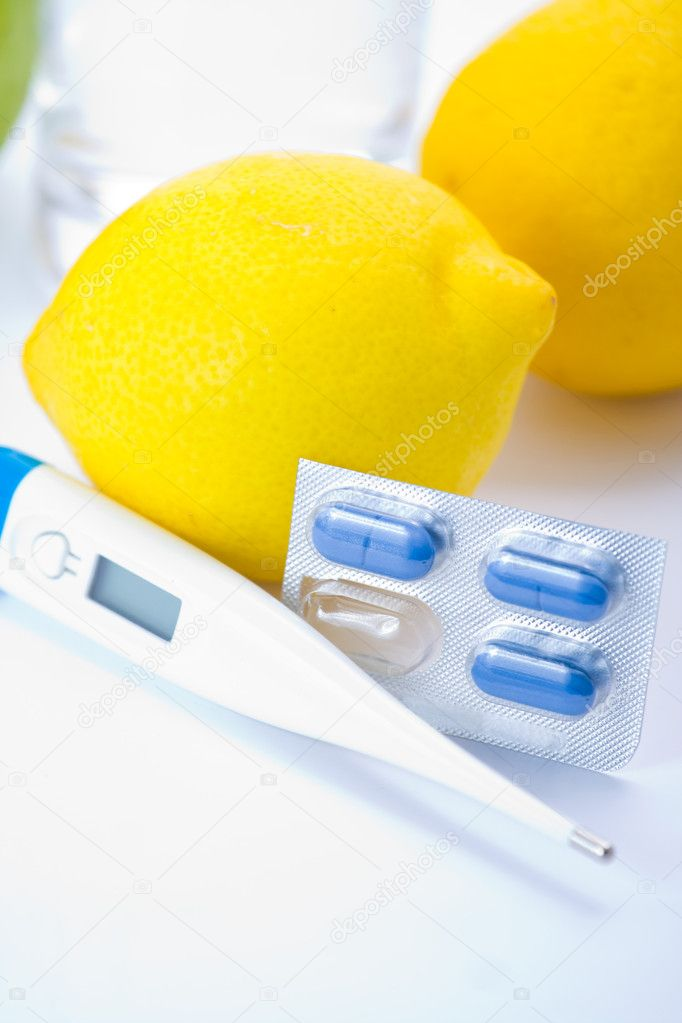 Thermometer, lemons and pills representing illness over white. — Stock Photo #1915630