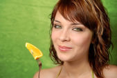 Girl and orange on a fork — Stock Photo