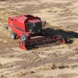 Stock Photo: Machine harvesting corn field
