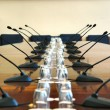 Microphones in empty conference hall — Stock Photo