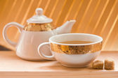 Teapot, a cup of tea and brown sugar — Stock Photo