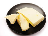 Butter on black butter dish isolated o — Stock Photo