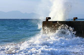 Wave breaking against stone mooring — Stock Photo