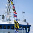 Signal flags on the mast of ship - Stock Photo