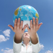 Woman holding a globe under blue sky — Stock Photo #1946006