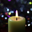 Light candle on dark background — Stock Photo