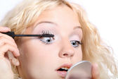 Beautiful woman applying black mascara o — Stock Photo