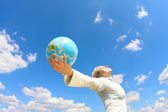 Woman holding a globe under.blue sky — Stock Photo