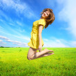 Stock Photo: Happy young womjumping in meadow