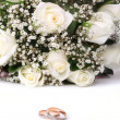 Wedding rings and roses bouquet — Stockfoto