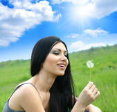 Beautiful woman blowing dandelion — Stock Photo