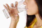 Beautiful woman drinks water from glass — Stock Photo