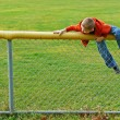 Young boy climbing chain link fence - Stock Photo