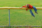 Young boy climbing chain link fence — Stock Photo