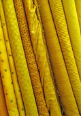 Assorted yellow fabrics background — Stock Photo