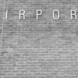 Generic airport sign on brick wall — Stock Photo
