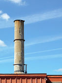 Crumbling concrete smokestack — Stockfoto