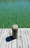 Pier post with shallow water — Stock Photo