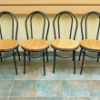 Empty chairs lined up against a wall — Stock Photo #2169005