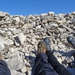 Stock Photo: Two hikers tired feet in rocky pit