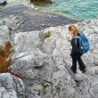 Blond womhiking on rocky coast — Stock Photo #2206109