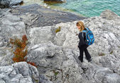 Blond woman hiking on rocky coast — Stock Photo