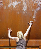 Blond woman with rusty metal background — Stock Photo