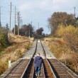 Young boy walking on train tracks — Stock Photo