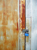 Weathered boathouse door with blue lock — Stock Photo