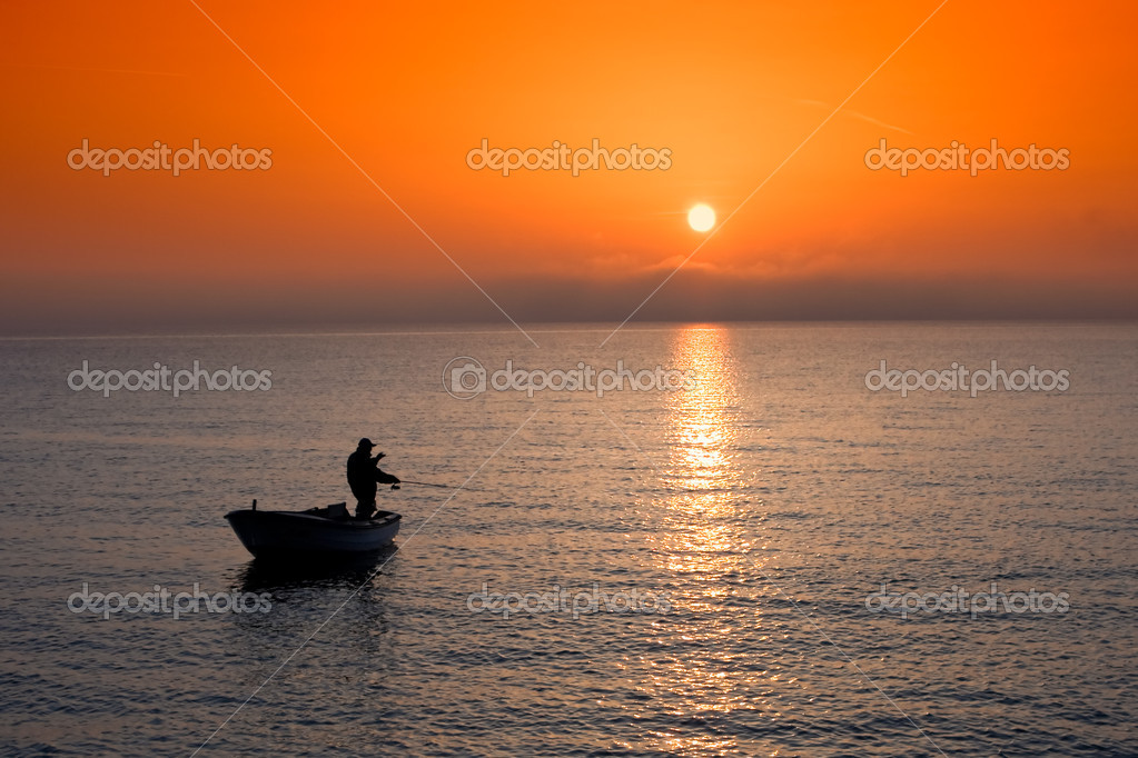 Man in a boat angling at sunset — Stock Photo #1960829