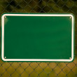 Fence with a blank green sign — Stockfoto
